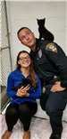 Young woman holding a kitten and Police Officer with kitten perched on his shoulder