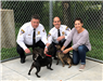 Cpt. Drumm, Chief Marshuetz and resident play with 3 of the dogs at the shelter