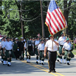 Band with bagpipes and drums marches in the Memorial Day Parade