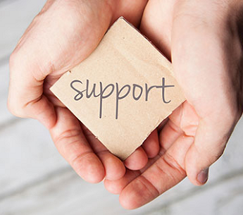"""Support"" written on a wooden block, held in hands"