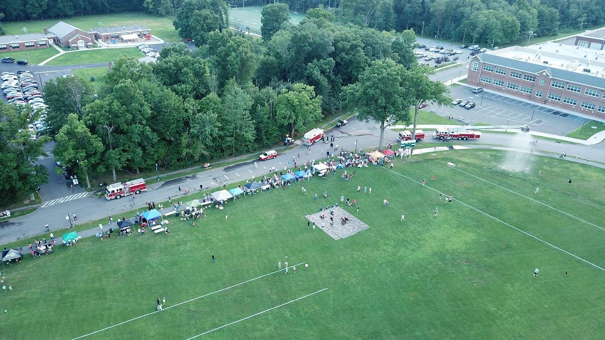 Aerial photo of side of Oval with people, tents, activities, and fire trucks below